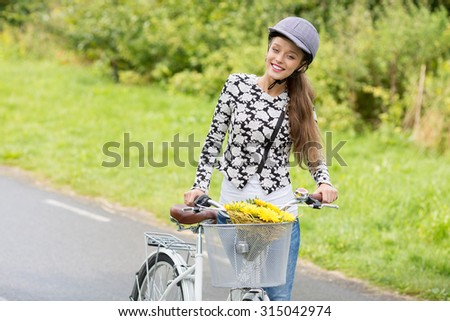 Teenage girl standing with city bicycle and bouquet of flowers.