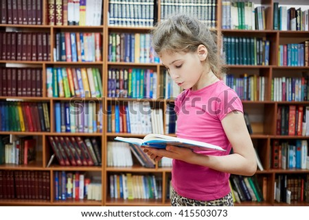Teenage girl stands in library room with bookshelves reading book.