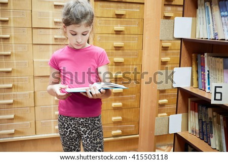 Teenage girl stands reading book near bookshelves in library. - stock photo