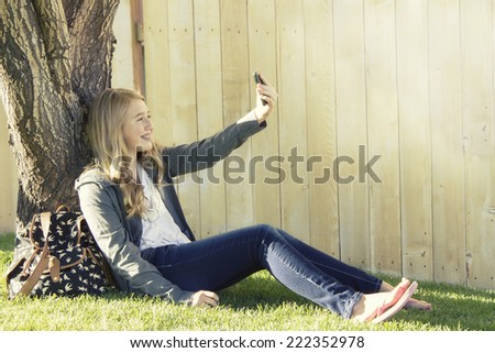 Teenage girl taking a selfie with a cell phone in an outdoor setting - stock photo