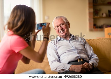 Teenage girl taking photo of her smiling grandfather with mobile phone at home