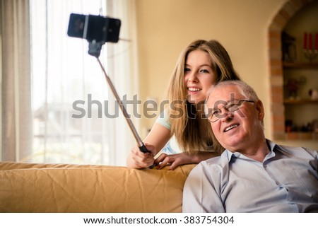 Teenage girl taking photo with mobile phone on selfie stick of herself and her grandfather at home - stock photo