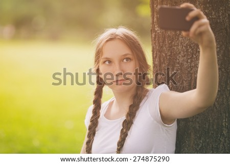 teenage girl taking selfie using mobile phone in park under the tree - stock photo