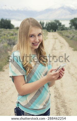 Teenage girl using cellphone walking down a country dirt road outdoors in a rural area, with Instagram or vintage filter.
