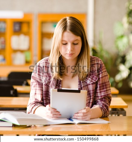 Teenage girl using electronic tablet at library - stock photo