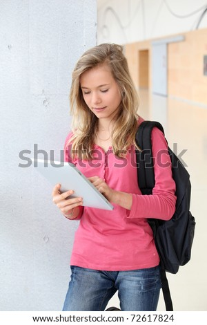 Teenage girl using electronic tablet at school - stock photo