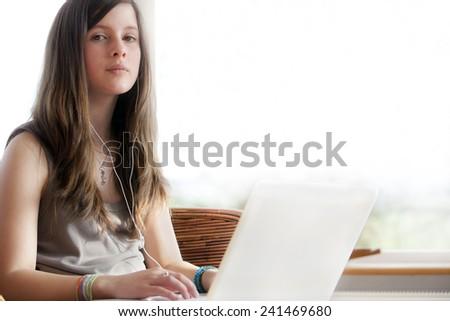 Teenage girl using laptop - stock photo