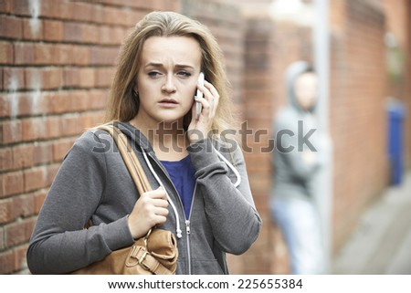 Teenage Girl Using Phone As She Feels Intimidated On Walk Home - stock photo