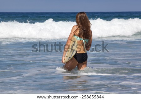 Teenage Girl Walking in the Waves with Her surfboard