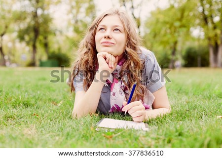 Teenage girl wearing checkered shirt and scarf lying down on grass in autumn park with notebook and pen in her hand and dreaming - inspiration concept - stock photo