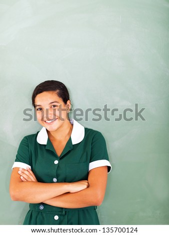 teenage girl wearing school uniform standing in front of chalkboard