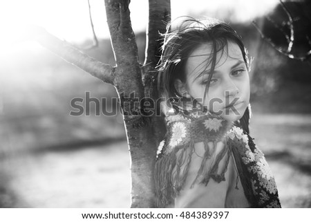 Teenage girl wearing shawl leaning against tree in countryside, black and white photograph.