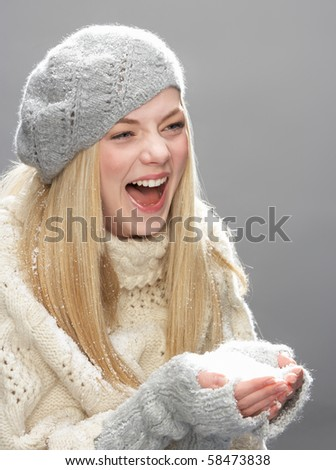 Teenage Girl Wearing Warm Winter Clothes And Hat Blowing Snow In Studio - stock photo