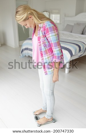 Teenage girl weighing herself - stock photo