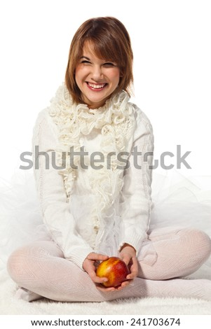 Teenage girl, who is wearing white knitwear items, is holding  the ripe red apple in his hands, isolated on white background  - stock photo