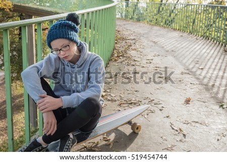 Teenage girl with an attitude sitting on her skateboard on an urban footpath ramp, copy space on the right