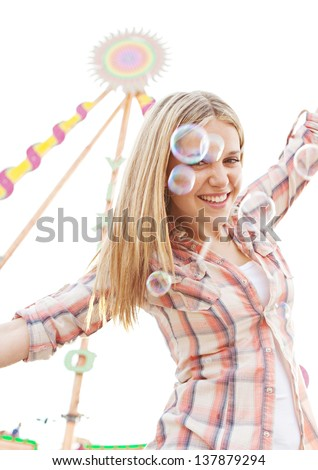 Teenage girl with arms outstretched being playful in an attractions park ground during a sunny day with soap bubbles floating in the air. - stock photo