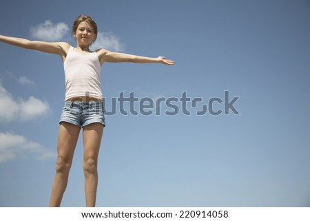 Teenage girl with arms outstretched under blue sky - stock photo