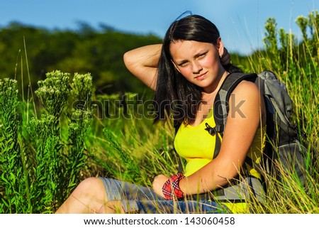 Teenage girl with backpack sitting in summer grass - stock photo