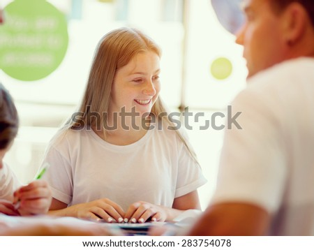 Teenage girl with books studying in library - stock photo