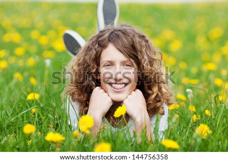 teenage girl with curls relaxing in nature - stock photo