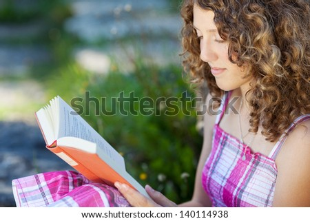 teenage girl with curly hair reading a book outside - stock photo