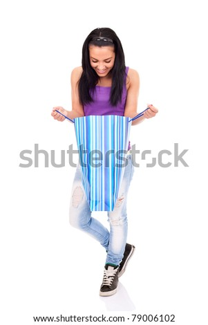 teenage girl  with gift, looking in bag and smiling, isolated on white background - stock photo