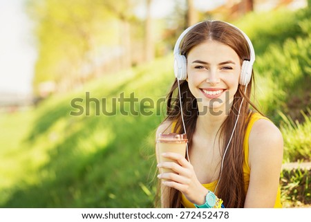 Teenage girl with headphones and takeaway coffee outdoors on sunny summer day smiling. Beautiful millennial young woman listening to music relaxing. Horizontal, retouched, vibrant colors. - stock photo
