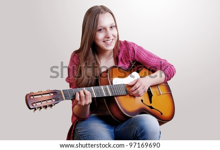 Teenage girl with long hair playing by old guitar