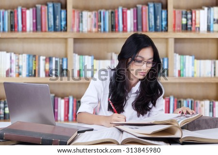 Teenage girl with long hair sitting in the library while studying and doing her school assignment with books and laptop - stock photo