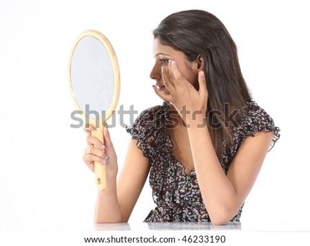 teenage girl with makeup mirror adjusting her makeup - stock photo