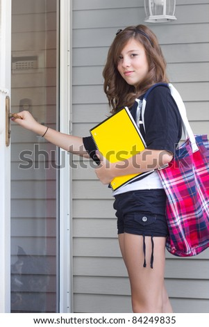 Teenage girl with notebook and book bag returning home from school - stock photo