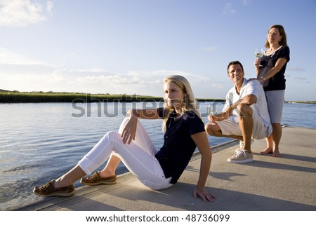 Teenage girl with parents on dock by water relaxing on sunny day