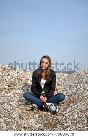 Teenage girl with rollerblades sitting on pebbles