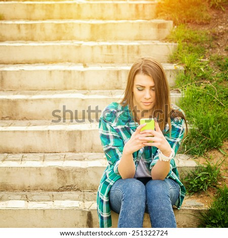 Teenage girl with smartphone sitting on stairs in park texting. Young Caucasian woman outdoors in summer using cellphone. Retouched, filter, vibrant colors, square format, copy space. - stock photo