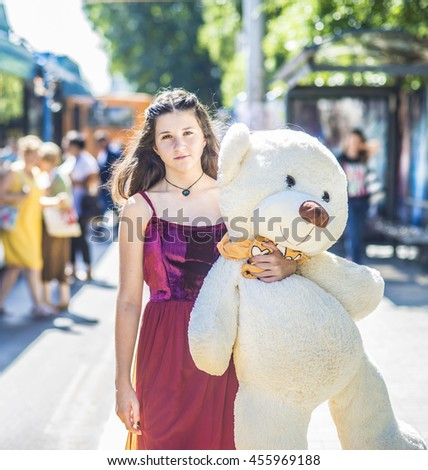 Teenage girl with teddy bear on street