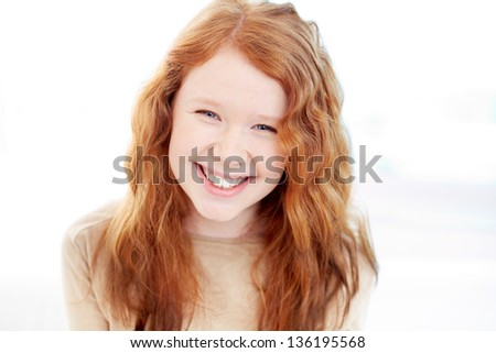Teenage girl with wavy ginger hair looking at camera with smile - stock photo