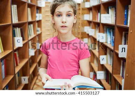 Teenage girl with wide open eyes stands holding book between bookcases in libray.