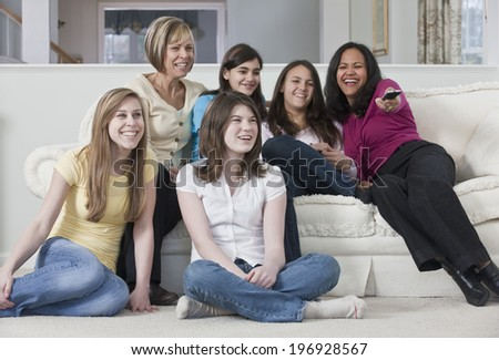 Teenage girlfriends at home with family on a sofa