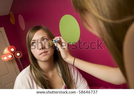Teenage girls apply makeup in their room. - stock photo