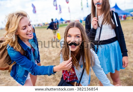 Teenage girls at summer festival with fake mustache - stock photo