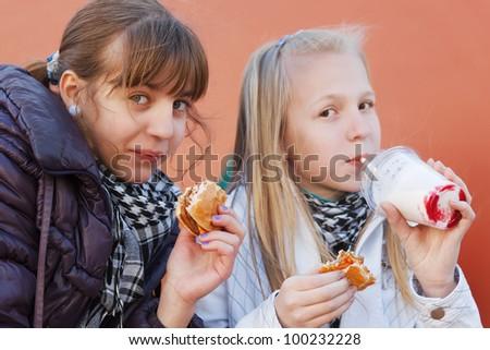 Teenage girls eating a burgers - stock photo
