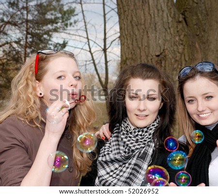 Teenage girls having fun with soap bubbles in the park - stock photo