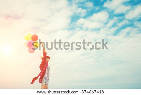 Teenage girls holding colorful balloons in the bright sky and smiled happily. - stock photo