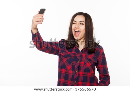 Teenage girls in hipster outfit make selfie on a phone. Isolated studio portrait on whited background. - stock photo