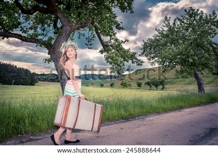 teenage girls on rural road with a suitcase - stock photo