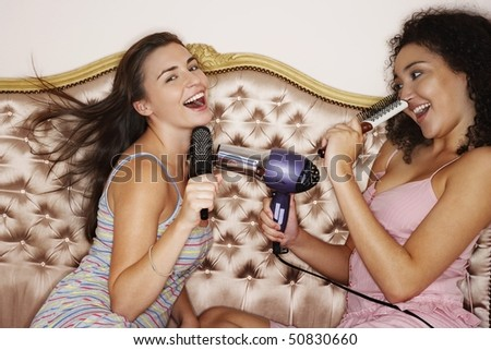 Teenage Girls playing with brushes and hair dryer at slumber party - stock photo