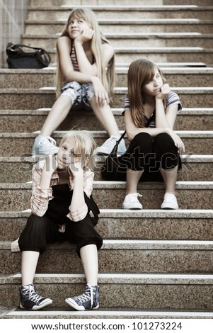 Teenage girls sitting on a steps - stock photo