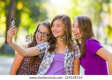 Teenage girls taking selfie in park with mobile phone - stock photo