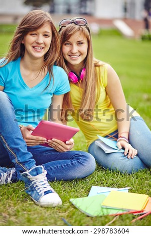 Teenage girls with touchpad relaxing on green lawn